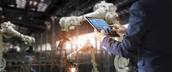 engineer holding iPad by automated assembly line