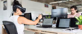 woman in VR headset designing product on laptop