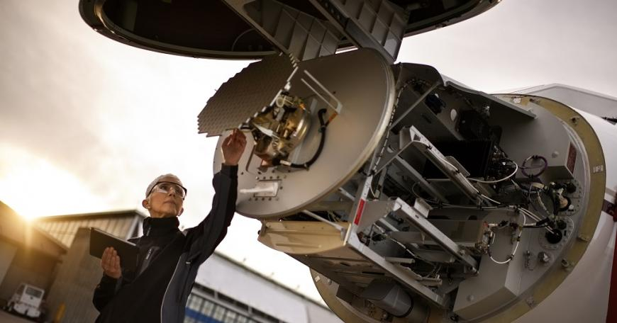 Woman wearing safety goggles, examining aerospace part