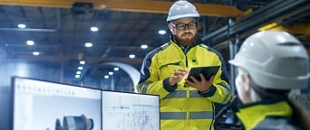 engineer in hardhat with iPad meeting with engineer at desktop